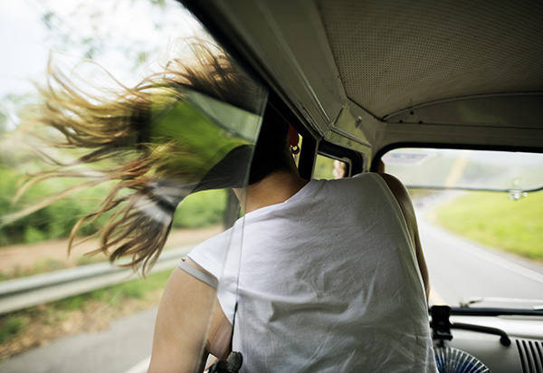 Kvinde sidder i bil med hovedet ud af vinduet